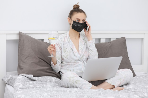 Woman with with a glass of water working from home and wearing protective mask.