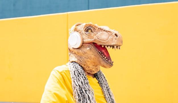 Женщина с маской t-rex и наушниками слушает музыку на желто-синей стене