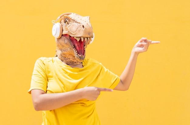 Женщина с маской t-rex и наушниками, указывая копией пространства на желтом фоне