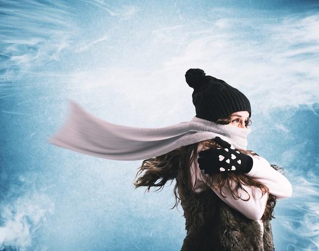 Женщина в шерстяном шарфе и шапке пытается укрыться от зимних холода