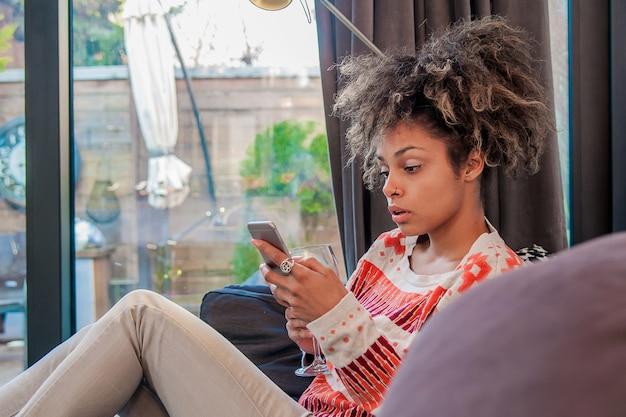 電話で心配している表現の女性。ショックを受けた若い女性を強調し、携帯電話で話し、不愉快な会話をして悪い知らせを受ける