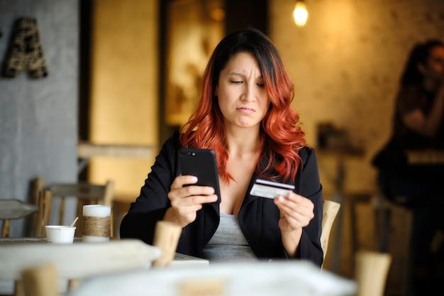 Женщина с обеспокоенным лицом смотрит на свой мобильный телефон, держа в руке кредитную карту