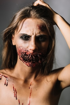 Woman with wounded face scratching head
