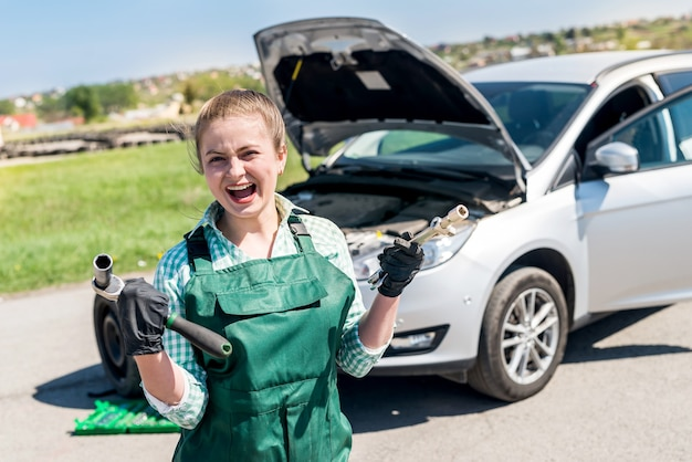 Woman with wrenches and car with open hood