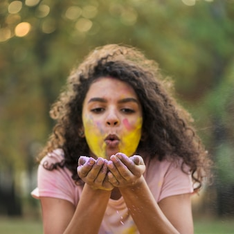 Woman with yellow covered cheeks blowing paint