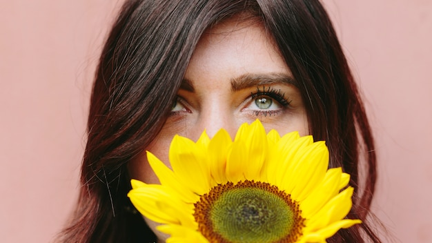 顔の近くの黄色い花を持つ女性
