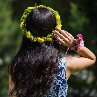 Woman with yellow flower wreath in the head.