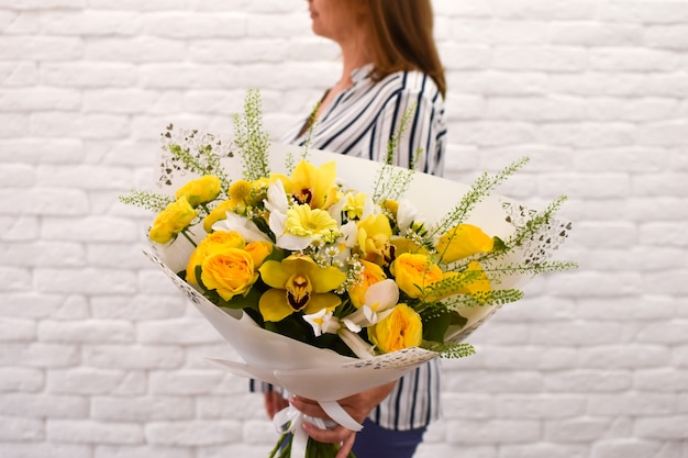 Woman with yellow flowers. bouquet of beautiful bright flowers.