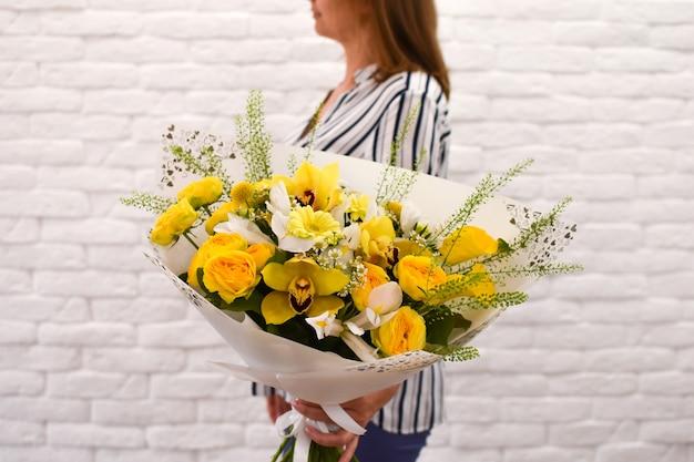 黄色い花を持つ女性。美しい鮮やかな花の花束。