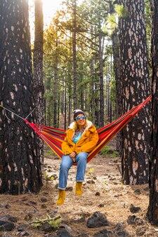 黄色いジャケットを着た女性は、森の森のカラフルなハンモックに座って休憩し、アウトドアレジャー活動や、週末や休暇の冒険を楽しんでいます-人と自然