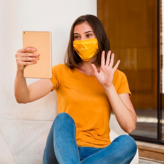 Woman with yellow mask waving at tablet