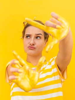 Woman with yellow painted hands