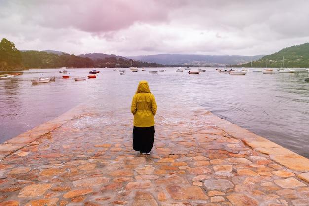 노란색 비옷을 입은 여성이 뒤로 서서 놀라운 전망을 바라보고 있습니다.