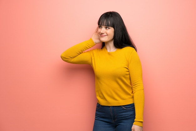 Woman with yellow sweater over pink wall listening to something by putting hand on the ear