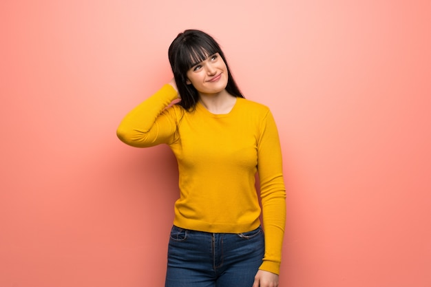 Woman with yellow sweater over pink wall thinking an idea while scratching head