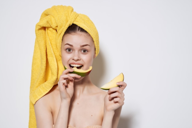 Woman with yellow towel on her head eating mango bare shoulders vitamins