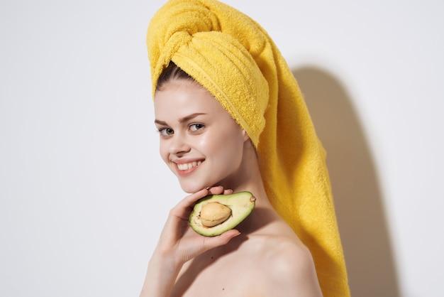 彼女の頭に黄色いタオルを持つ女性アボカドきれいな肌のフルーツダイエット