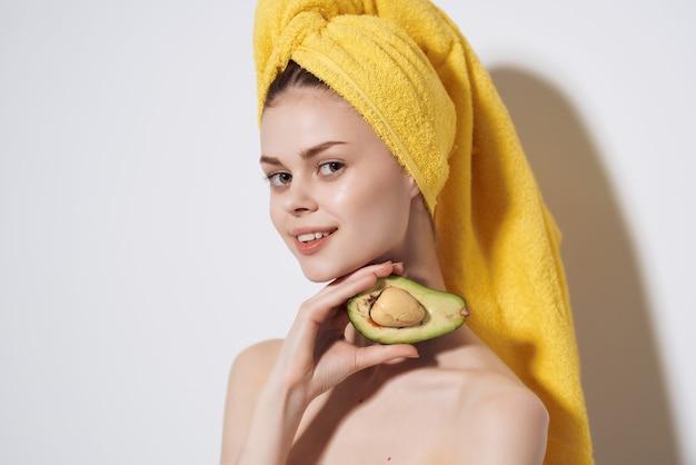 그녀의 머리에 노란색 수건을 가진 여자 아보카도 깨끗한 피부 과일 다이어트