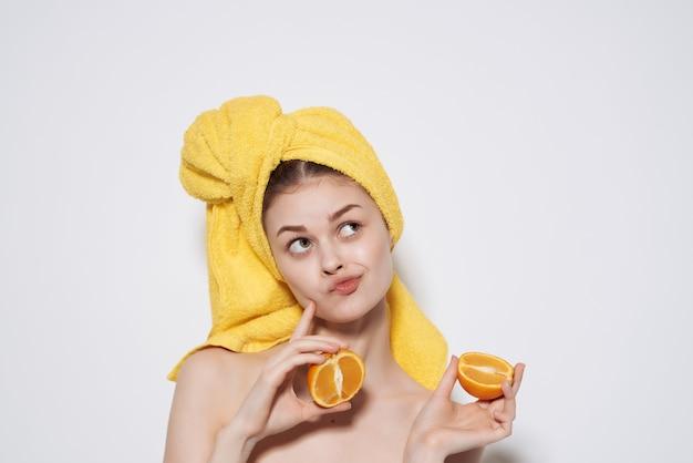 그녀의 머리에 노란색 수건을 가진 여자 오렌지 과일 깨끗한 피부. 고품질 사진