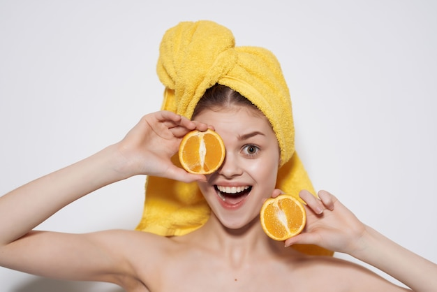 Женщина с желтым полотенцем на голове апельсины фрукты чистая кожа