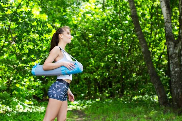 Женщина с ковриком для йоги в парке