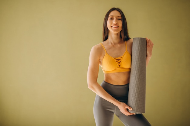 Woman with yoga mat practising yoga