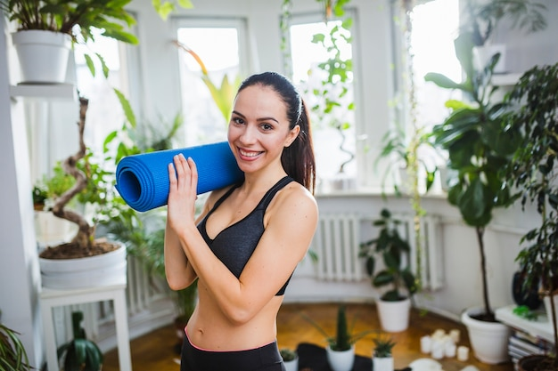 Woman with yoga mat of shoulder