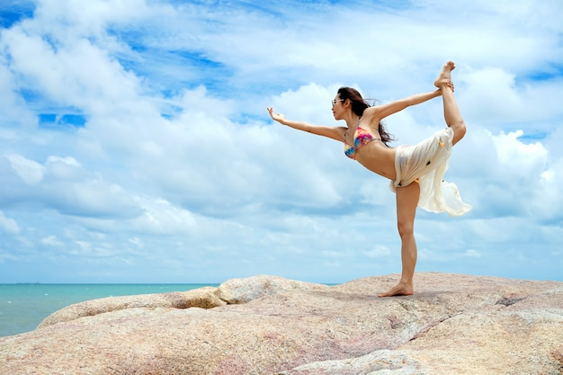 The woman with yoga posture on the beach