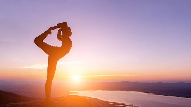 Woman with yoga posture on the mountain at sunset
