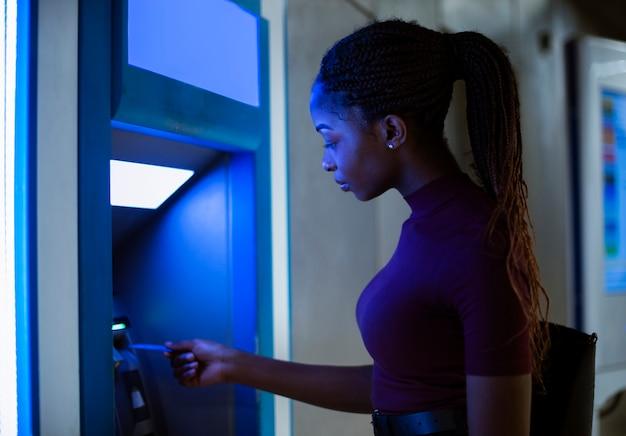 현금 인출기에서 돈을 인출하는 여자 프리미엄 사진