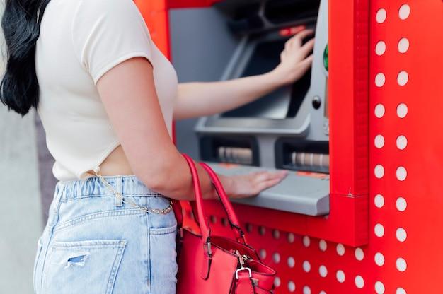 Atm에서 신용 카드로 돈을 인출하는 여자가 닫힙니다.