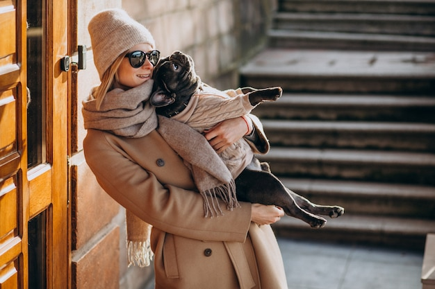 Woman withg her pet french bulldog walking out