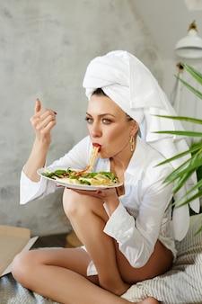Женщина без комплексов ест дома пиццу и спагетти. радость и смех на лице женщины