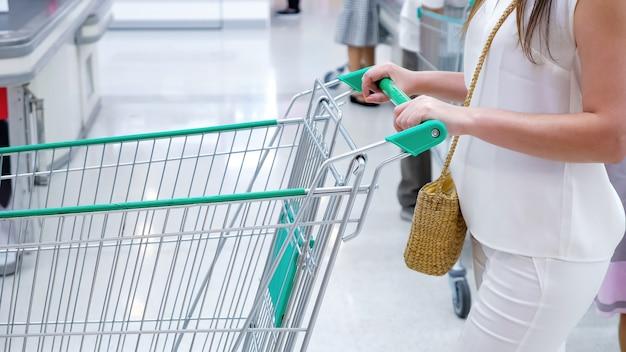 店内でトロリーを持った顔のない女性。認識できない買い物客が通り過ぎます。