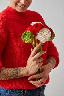 흰색 바탕에 문신이 있는 손에 꽃다발을 들고 얼굴이 없는 여자. 아름다움, 패션 개념입니다.
