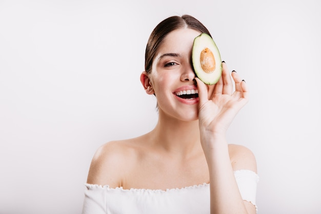 Woman without makeup with clean skin is smiling, posing with slice of avocado for portrait on white wall.