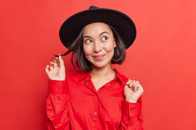 夢のような表情で化粧をしていない女性は、鮮やかなスタジオで屋内でポーズをとる黒い帽子の赤いシャツを着た素晴らしいカールの髪を考えています