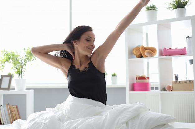 女性は朝目が覚め、笑顔が伸びる