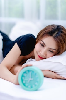 The woman woke up in the morning with a bright smile. and an alarm clock placed on the bed
