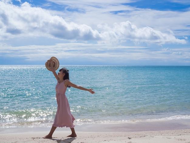 푸른 바다와 푸른 하늘 모래 해변에 wolking 여자. 여행 여름 휴가.