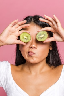 Woman wondering and covering her eyes with kiwi