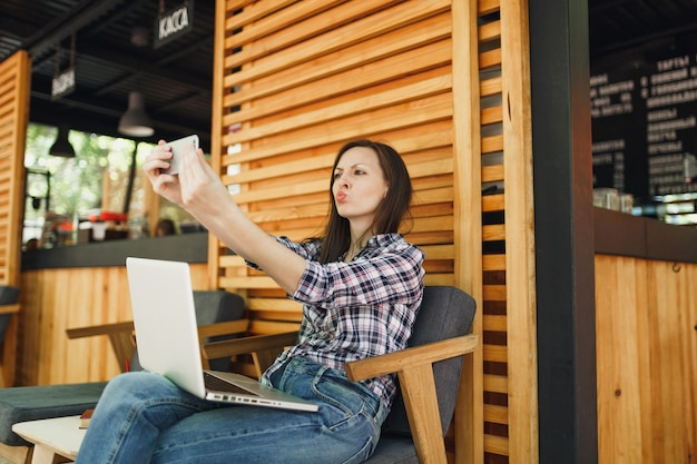 Woman in wooden outdoors street summer coffee shop sitting with laptop pc computer, doing selfie shot on mobile phone, relaxing during free time. mobile office