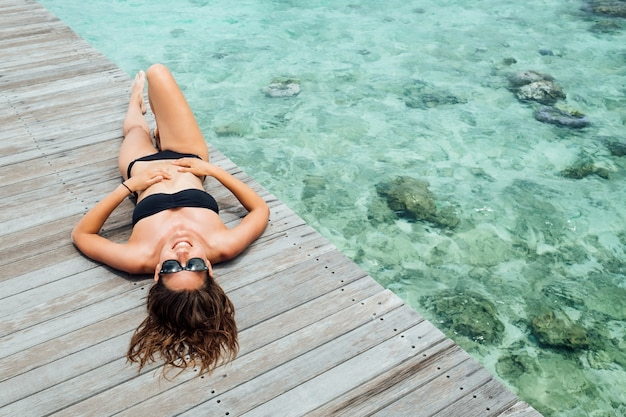Woman on wooden pier at sunny summer day, top view. young sexy woman in black bikini in summertime. summer beach vacation concept