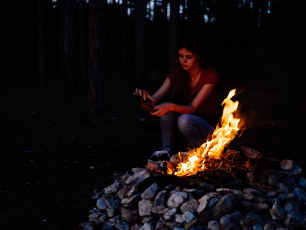 Woman in the woods near the campfire rest nature evening