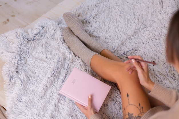 Woman in wool sock and sweater with pink notebook sign 2021, large tattoo on hip. female sit on bed at home in bedroom.
