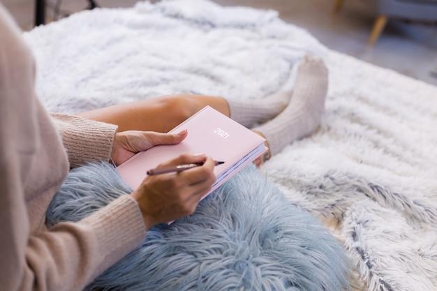 Donna in calza di lana e maglione con taccuino rosa segno 2021, grande tatuaggio sul fianco. la donna si siede sul letto a casa in camera da letto.