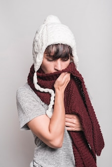 Woman in woolly hat covering her mouth with woolen scarf against gray background