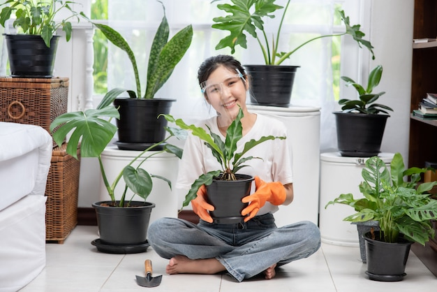 The woman wore orange gloves and planted trees in the house.