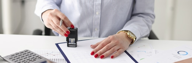 Woman at work desk puts stamp on documents business agreements strategy development concept