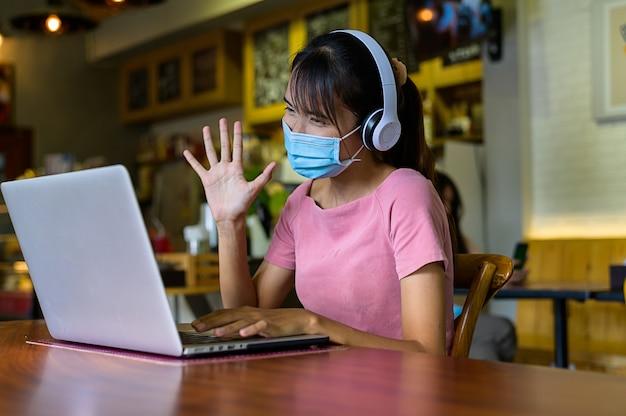 마스크 보호를 착용하고 가정에서 일하는 여성은 집에서 곧 전염병 상황이 개선되기를 기다립니다. 코로나 바이러스, covid-19, 재택 근무 (wfh),